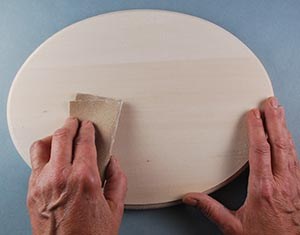 sanding a wood carving board